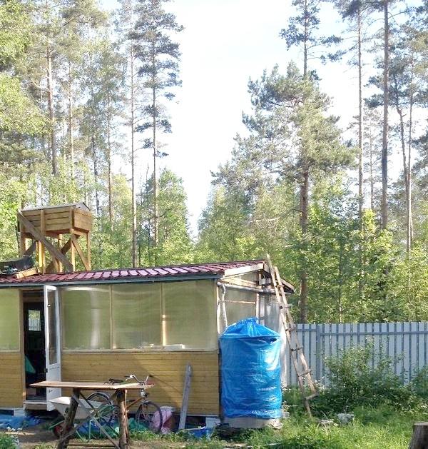 Водозбірна бочка (зліва від будинку під синім тентом) на даху -верхній бак