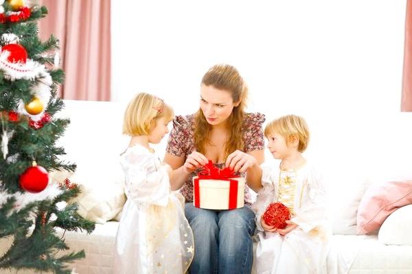 мама і дочки відкривають подарунок
