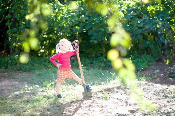 Дівчинка з лопатою на дачі